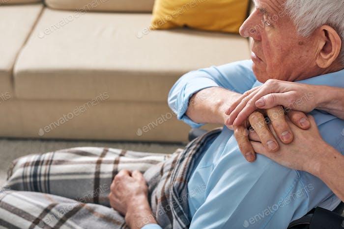 Mano del cuidador femenino joven en el hombro del hombre discapaciado mayor