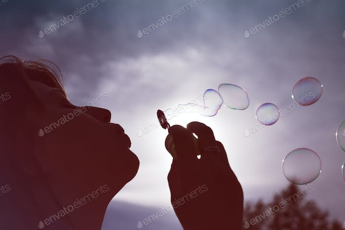 Low angle close up view of the silhouette of a woman blowing bubbles against a sunny blue sky.