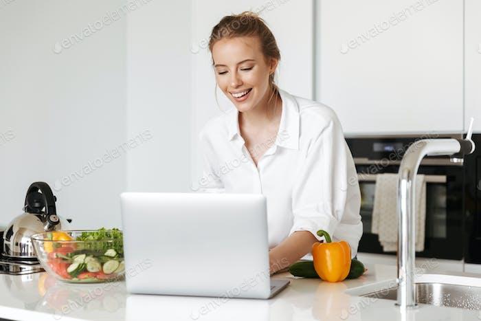 Glückliche junge Frau kochen Salat