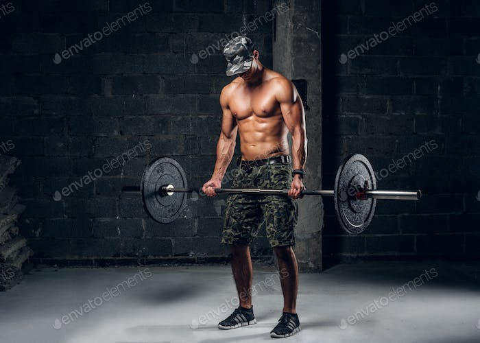 Man is doing exercises with heavy barbell