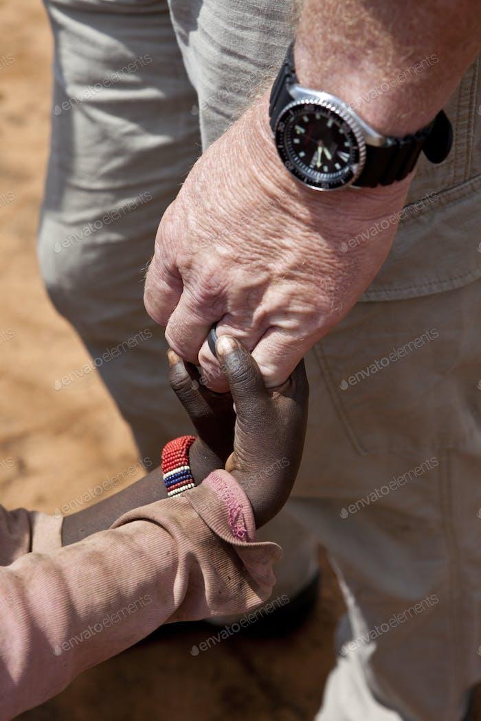 Helfer Hände halten Kinderhände