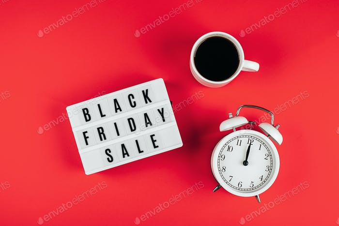 Black friday sale word on lightbox, cup of coffee, alarm on red background table. Flat lay