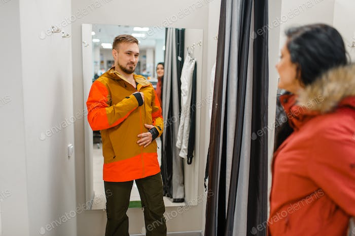 Couple trying on jackets for ski or snowboarding