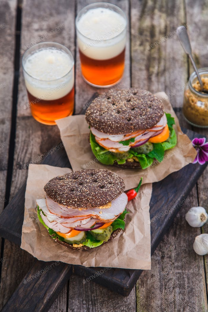 rye sandwiches with ham and letucce on wood table with two glasses of beer