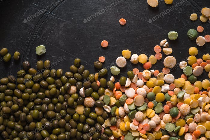 Placer Linsen und grüne Bohnen auf einem schwarzen Tisch