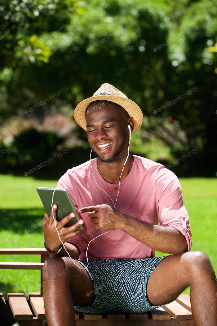 Junger afrikaner Mann sitzt im Freien mit einem digitalen Tablet