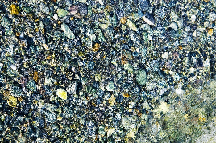 Kieselsteine mit Wasser bedeckt.