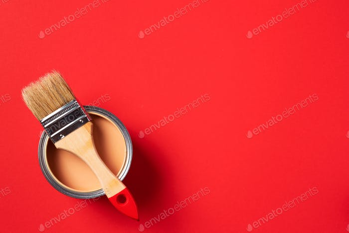 Brush and open paint can on trendy red background. Top view, copy space. Appartment renovation