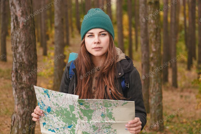 Woman with travel map and backpack in pine forest.