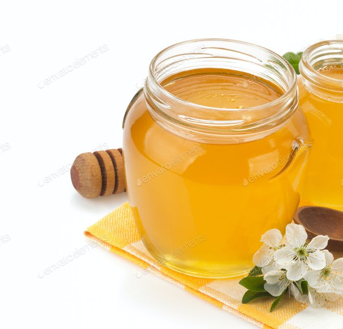 glass jar full of honey and stick