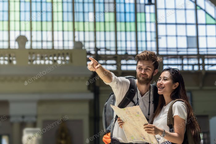 Multiethnic Travellers are looking the destination and holding the map at the train station