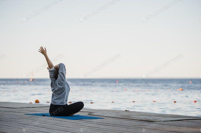 Hübsche Frau praktiziert Yoga an einem See