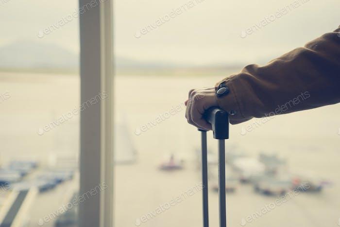 Mädchen hält Koffer im Flughafen