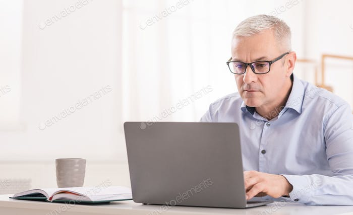 Serious senior man using laptop at office