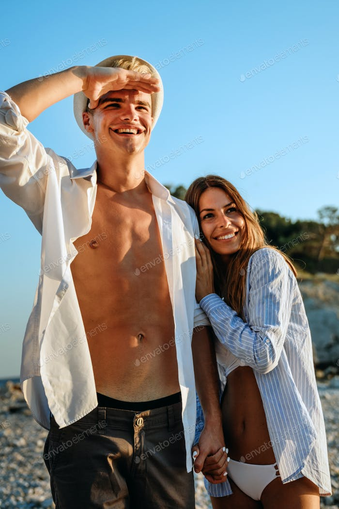 Couple walking on beach. Young happy people walking on beach smiling