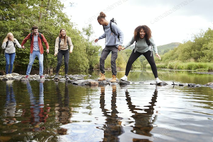 Multi ethnic group of five young adult friends laughing as they balance on rocks to cross a stream