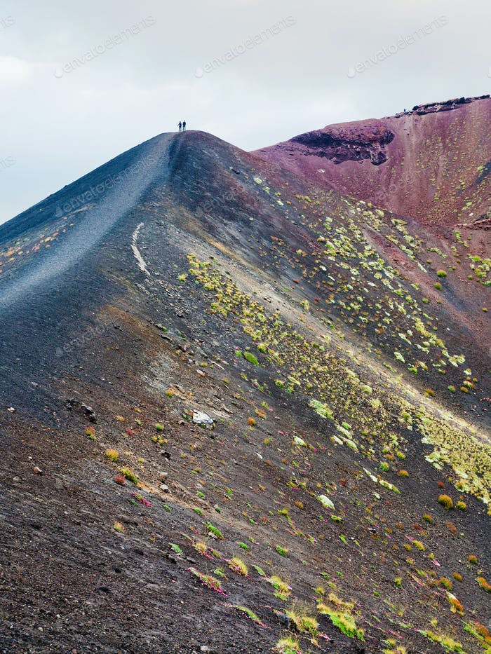 people on range between craters on Mount Etna