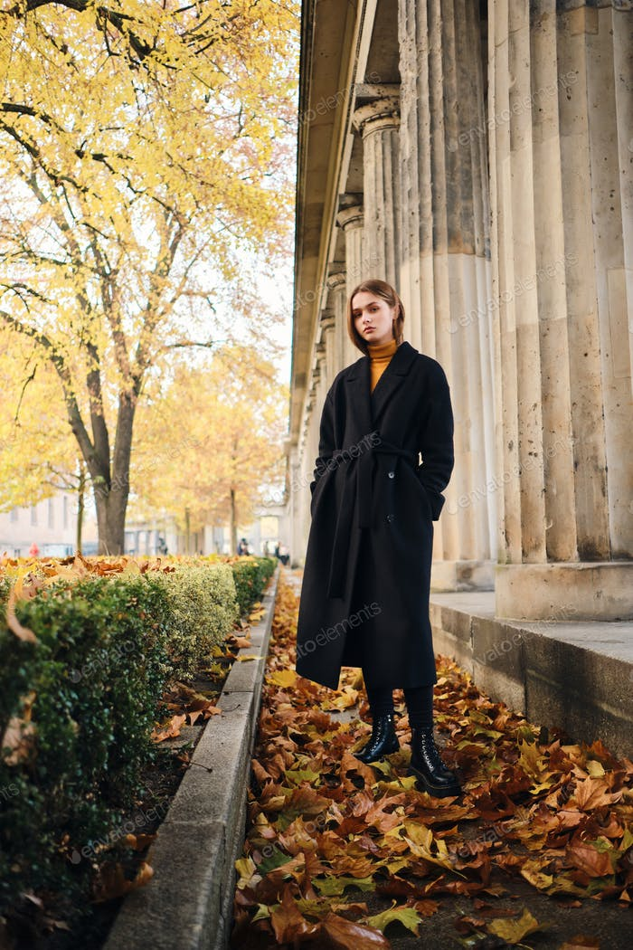 Gorgeous stylish girl in black coat resting in beautiful autumn city park