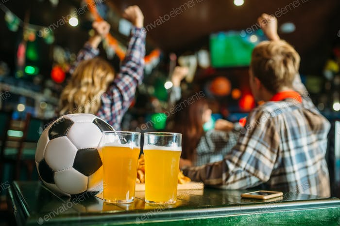 Ball and beer in sports bar, game watching concept