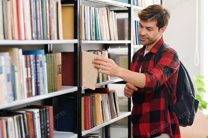 Young student with backpack taking one of books from shelf in library