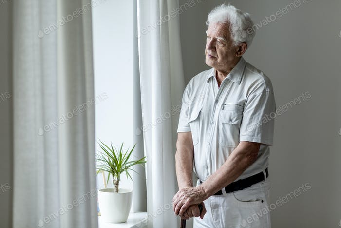 Lonely elderly man with walking stick standing by the window alo