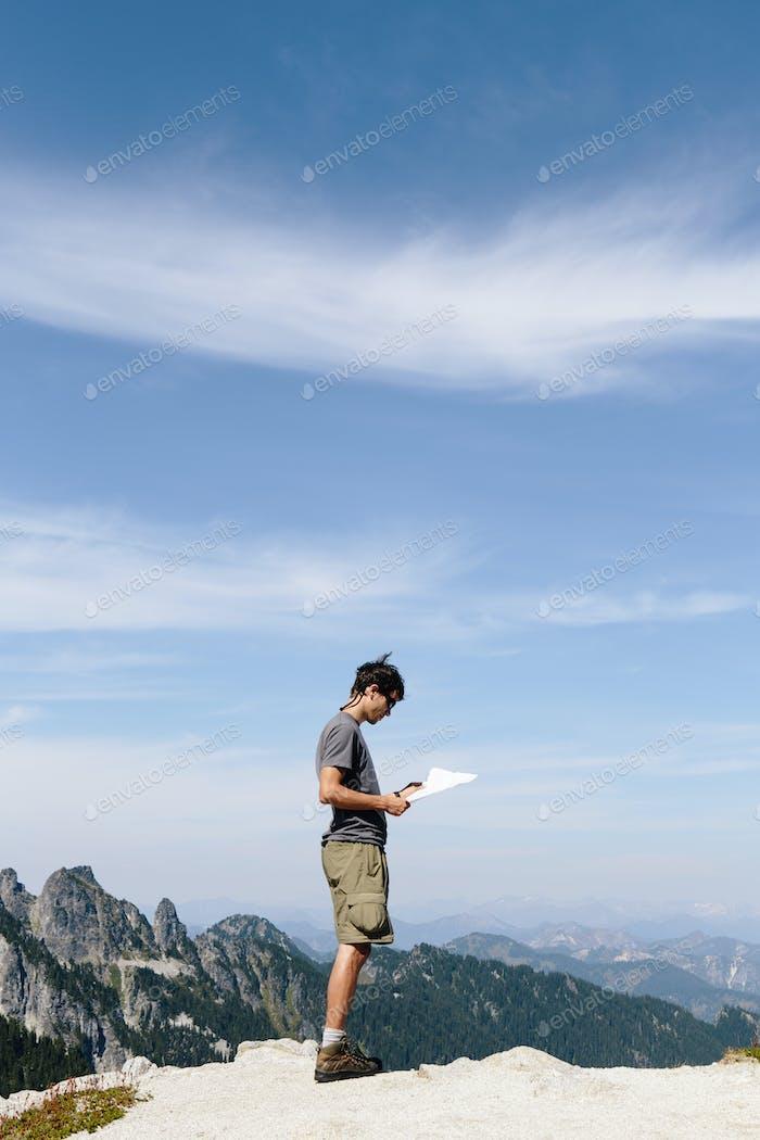 Ein Wanderer auf dem Berggipfel, Blick auf eine Karte. Überraschungsberg.