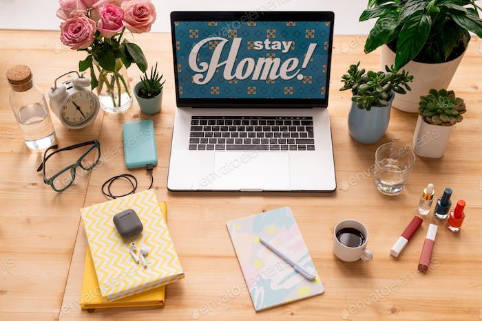 Stay home message on display of laptop on workplace of modern female designer