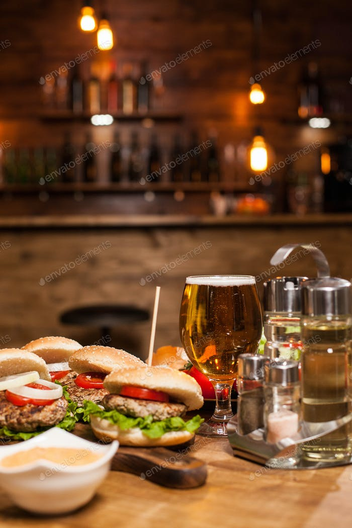 Cold beer with classic burgers on a restaurant wooden table