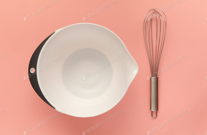 Whisk and a plastic cup for whipping on a pink background