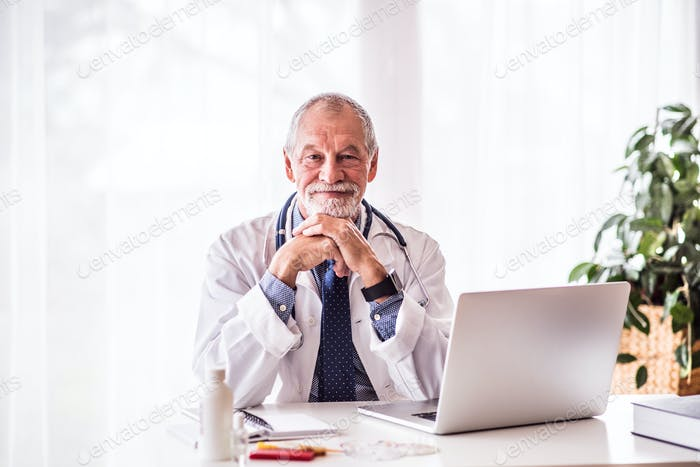 Senior doctor with laptop sitting at the office desk.