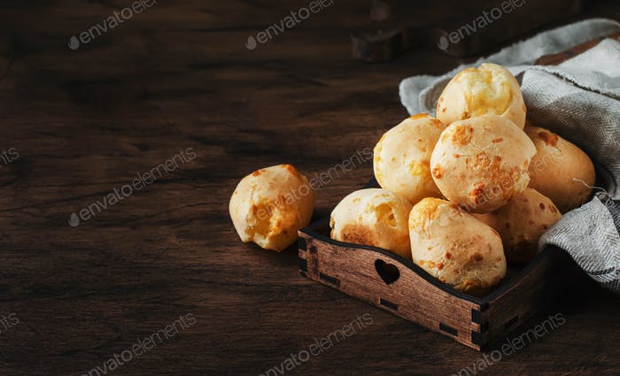 Cheese buns in wooden bowl, rustic kitchen table