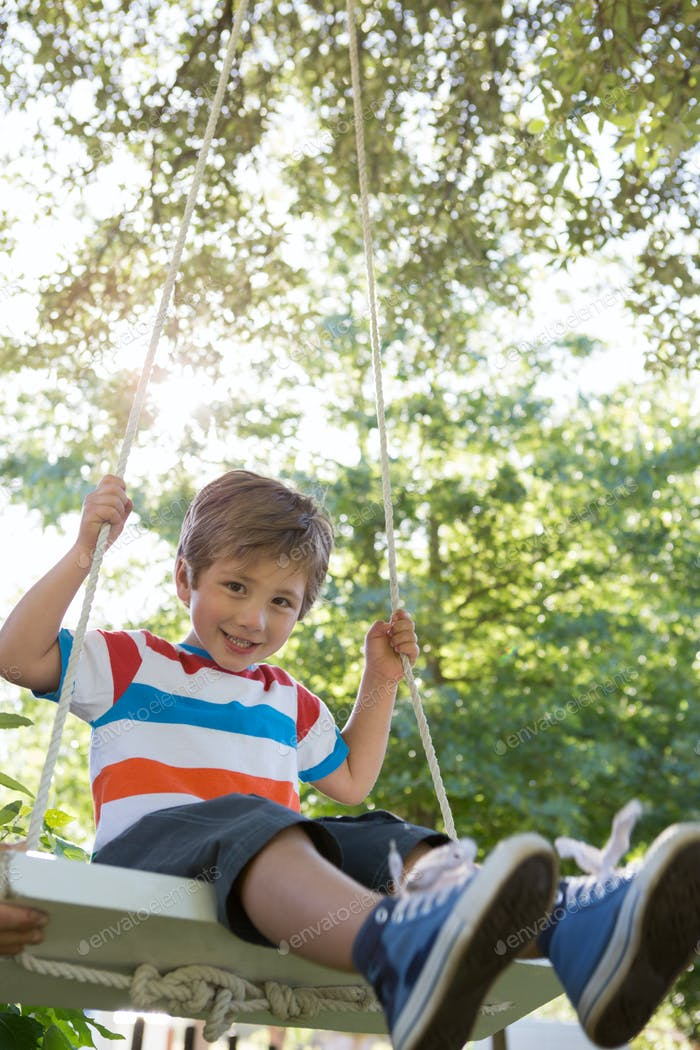 Happy little boy on a swing in the park on a sunny day