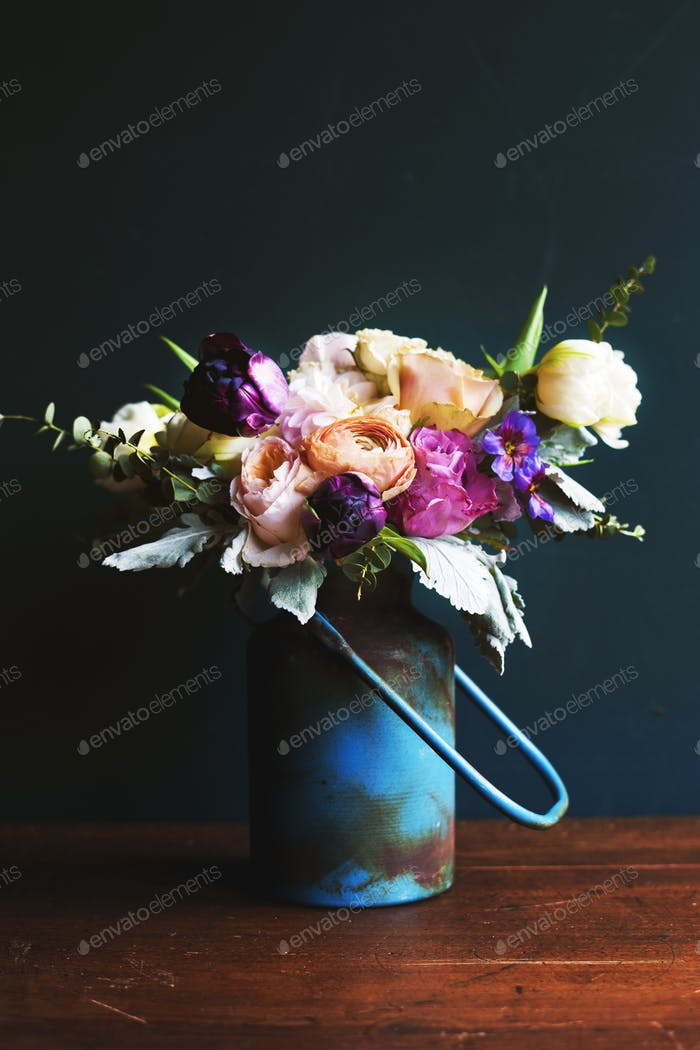 Various fresh flowers arrangement in metalic vase on wooden tabl