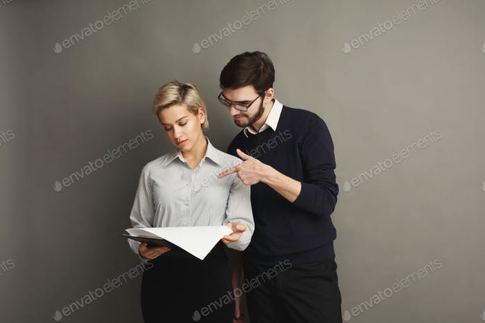 Serious couple in formal clothes on gray background