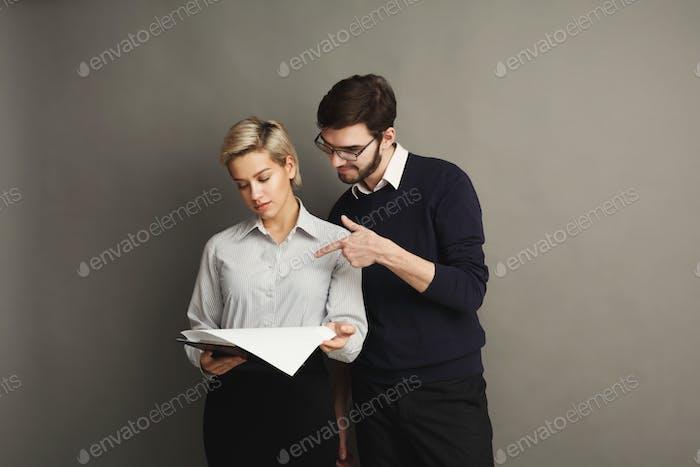 Ernstes Paar in formeller Kleidung auf grauem Hintergrund
