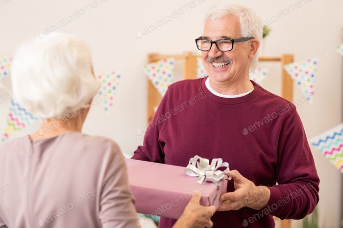 Happy retired man taking giftbox with present given by his wife