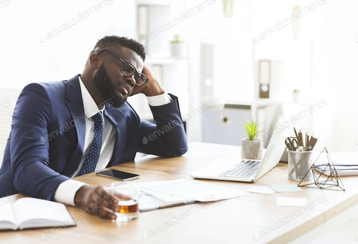 Young stressed businessman drinking whiskey in workplace