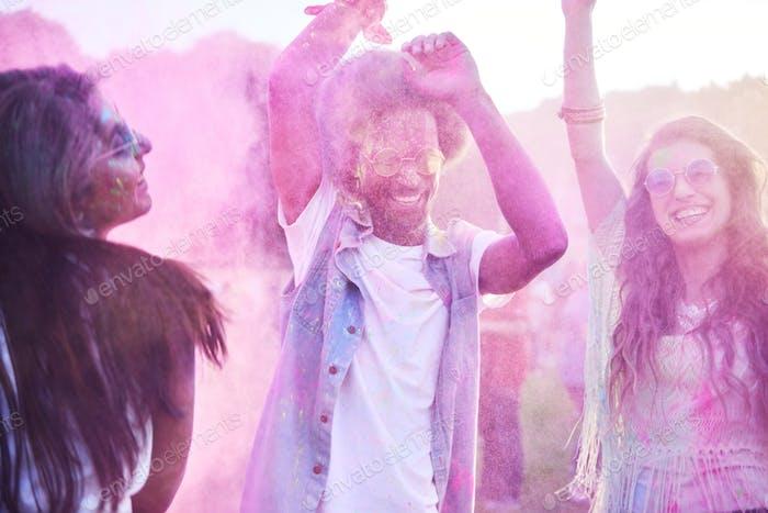 Bunte Freunde tanzen in Holi Farben