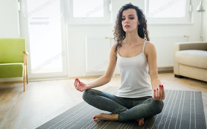 Young attractive woman relaxing and practicing yoga