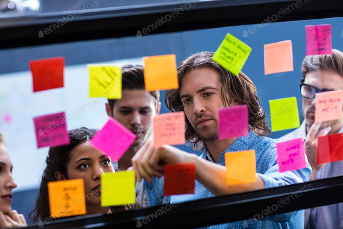 Hipsters reading a post it on a window