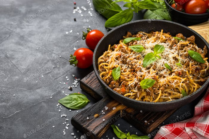 Pasta Bolognese in the skillet at black table