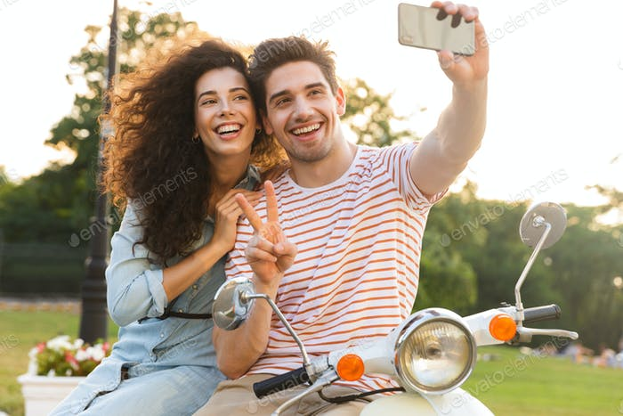 Photo of cute couple man and woman taking selfie on mobile phone