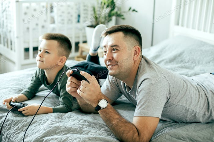 Smiling family son and dad playing video games and having fun together. Lifestyle, leisure concept
