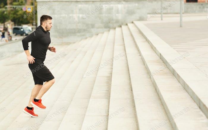 Morgen Workout. Junger Athlet läuft auf Treppen gegen Stadtbild