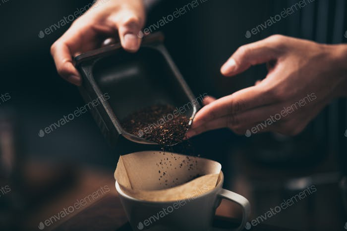 barista pouring coffee powder from a coffee grinder to a dripper to make fresh coffee in the café.