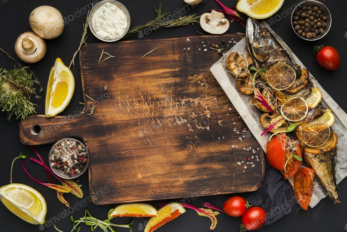 Grilled fish, cooking ingredients on wooden cutting board, top view