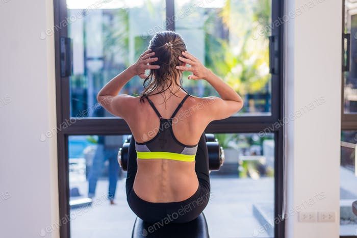 Attractive fit woman working out abs in fitness gym at luxury resort hotel with a great view during