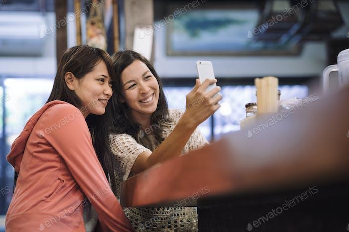 two female asian friends enjoying a traditional ramen restaurant in Kyoto Japan
