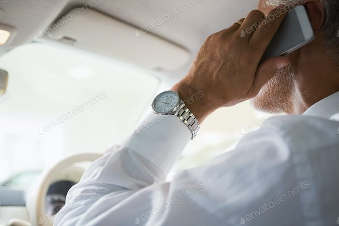 Close up of a businessman on the phone in his car at new car showroom
