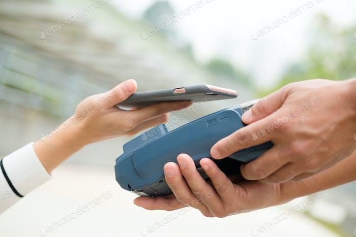 Frau zahlen mit Handy mit NFC-Technologie